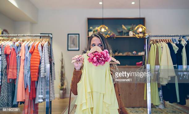 woman holding dress in a boutique - kleid stock-fotos und bilder