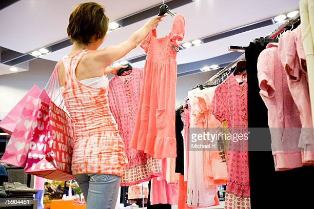 Woman holding dresses in boutique, rear view