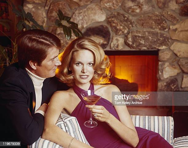 Woman holding drink beside man in living room