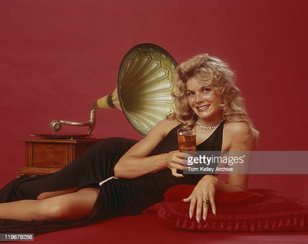 woman holding drink leaning beside gramophone, portrait - picture of phonograph stock photos and pictures