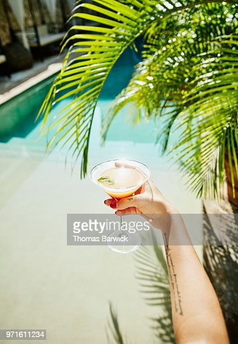 Woman holding drink with resort pool and palm fronds in background