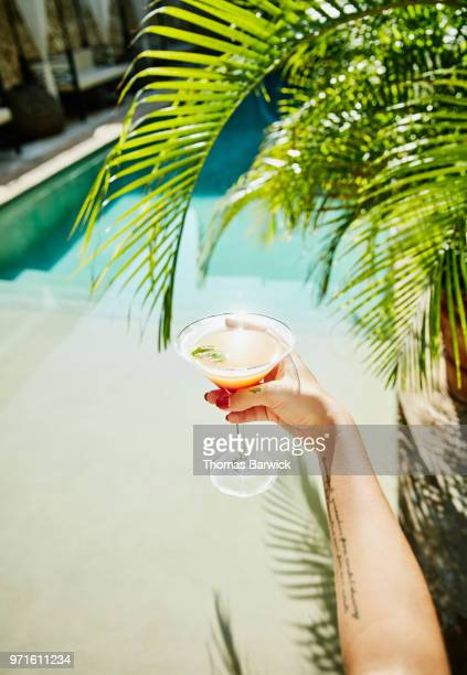 woman holding drink with resort pool and palm fronds in background - merida mexico stock photos and pictures