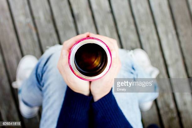 Woman holding drinks flask, high angle view