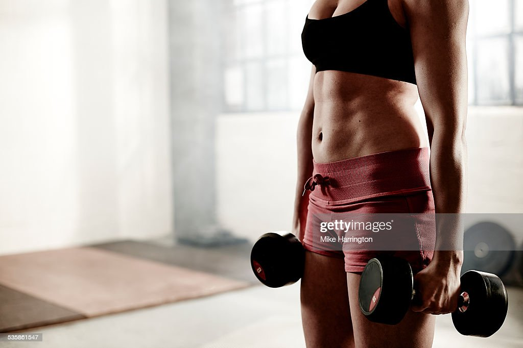 Woman holding dumbbells in gym. : Stock Photo