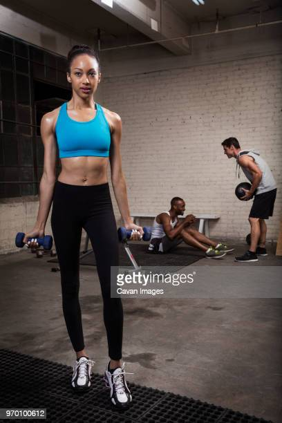 Woman holding dumbbells while standing with friends in background