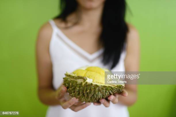 Woman holding durian on a green background
