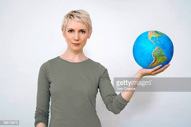 'Woman holding earth ball in hand, close-up'