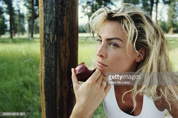 Woman holding eaten apple outdoors