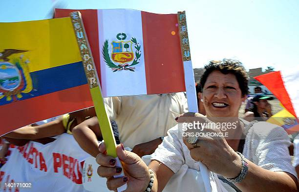A woman holding Ecuadorean and Peruvian flags wait the arrival of Peru's President Ollanta Humala and Ecuador's President Rafael Correa who take part...
