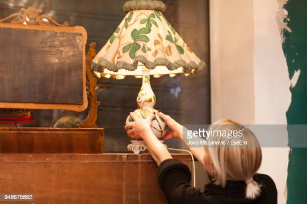 Woman Holding Electric Lamp On Wooden Table