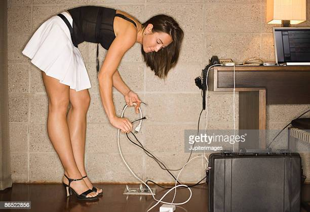 woman holding electrical plugs - beautiful women bent over stock photos and pictures