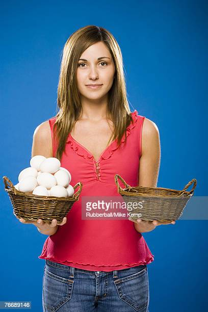 Woman holding empty basket and basket filled with eggs