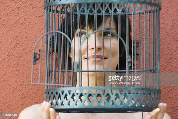 Woman holding empty birdcage in front of face, smiling, looking away