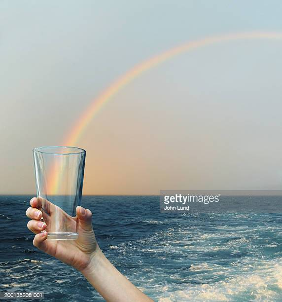 Woman holding empty glass, rainbow over ocean horizon in background