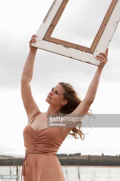 空の写真フレームを持つ女性