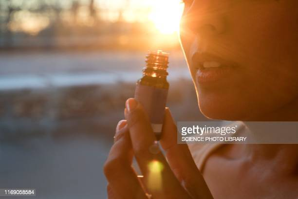 woman holding essential oil bottle - essential oil stock pictures, royalty-free photos & images
