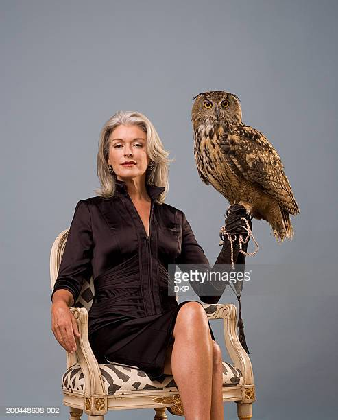 woman holding eurasian eagle owl (bubo bubo), sitting, portrait - beige glove stock photos and pictures