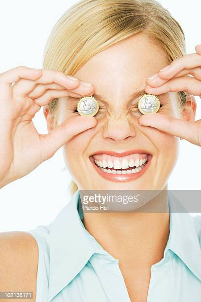 Woman holding euro coins in front of her eyes