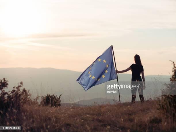 欧州連合の旗を掲げる女性 - ユーロ圏 ストックフォトと画像