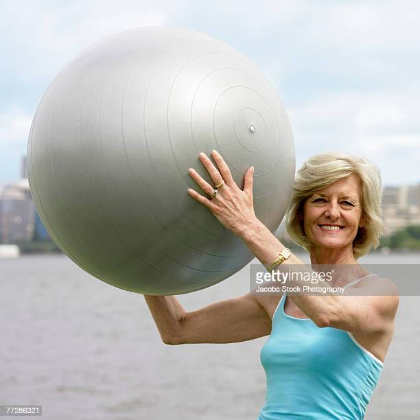 Woman holding exercise ball by the river