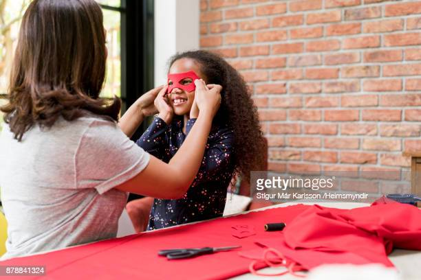 woman holding eye mask on smiling daughter's face - cloth face mask stock pictures, royalty-free photos & images