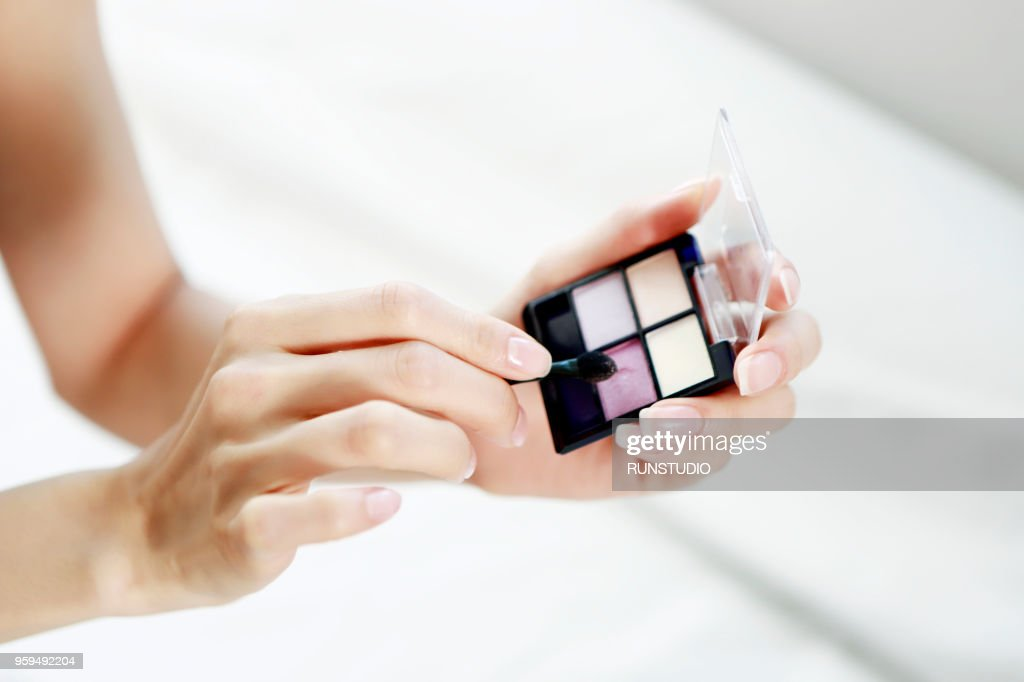 Woman holding eye shadow pallet and make up brush : Stock-Foto
