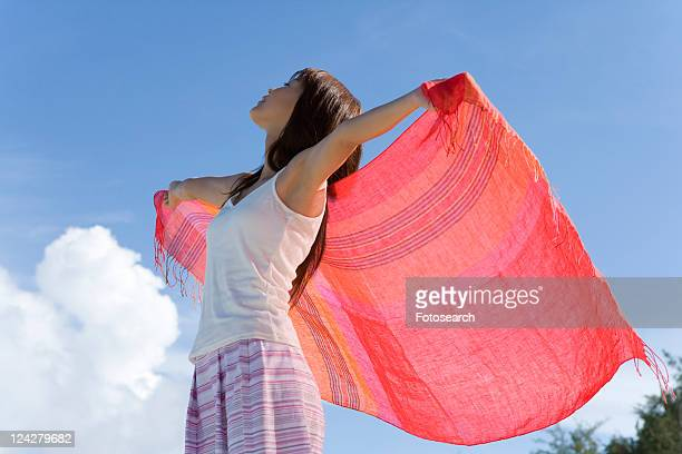 Woman holding fabric behind back on beach, closing eyes, Saipan, USA