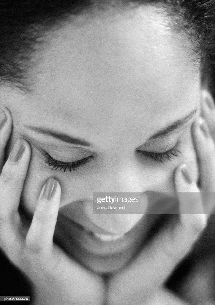 Woman holding face with hands, eyes closed, close-up, B&W. : Stockfoto