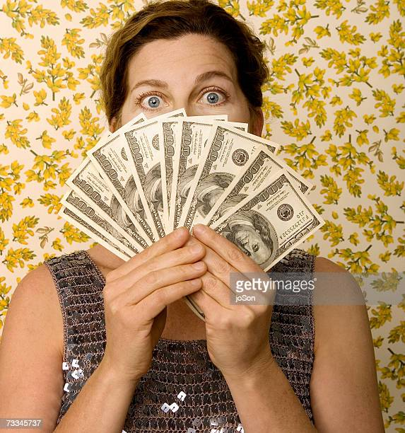Woman holding fan of American money