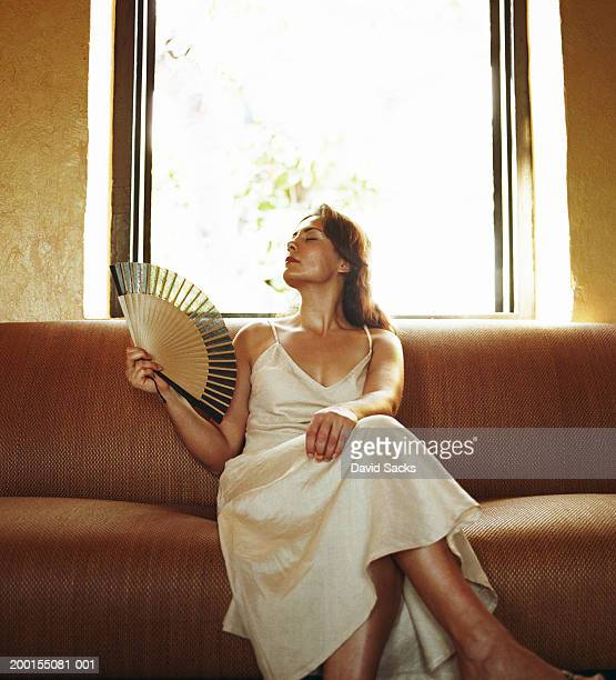 Woman holding fan on sofa