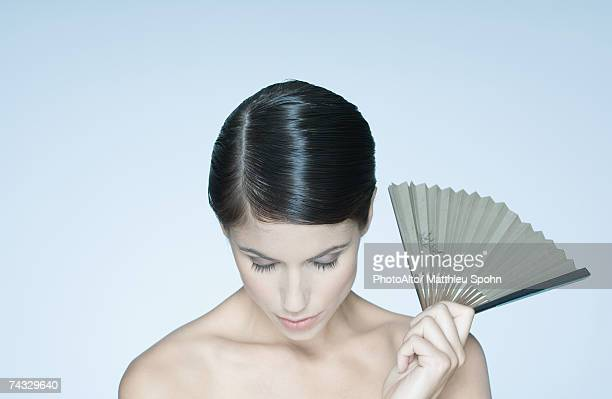 Woman holding fan, portrait