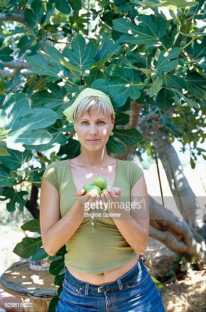 Woman Holding Figs in Front of Fig Tree