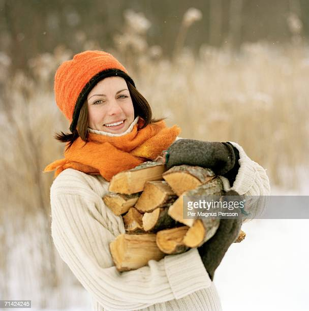 Woman holding firewood.