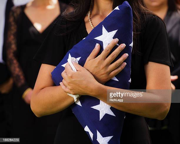woman holding flag at a funeral - military flags stock photos and pictures