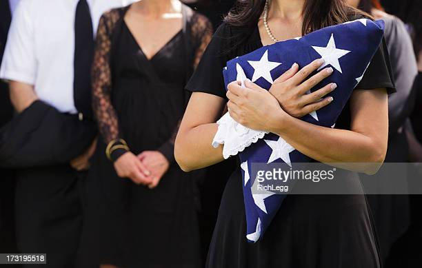 woman holding flag at a funeral - memorial event stock pictures, royalty-free photos & images