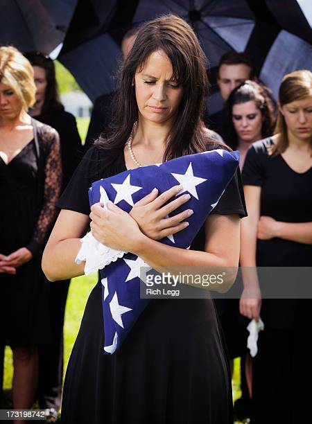 woman holding flag at a funeral - folded flag stock pictures, royalty-free photos & images