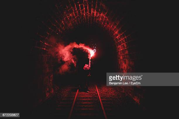 Woman Holding Flame Torch In Dark Tunnel