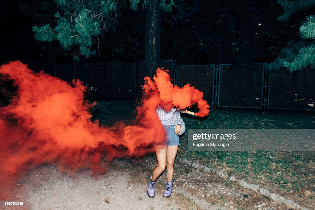 Woman holding flare in park at night : Stock Photo