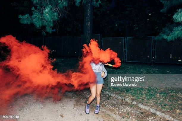 woman holding flare in park at night - opstand stockfoto's en -beelden