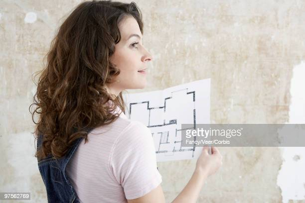 Woman holding floor plans