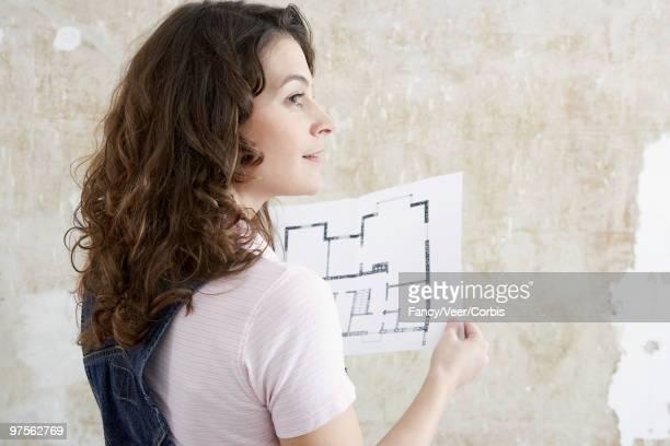 Woman holding floor plans