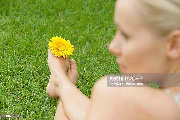 Woman holding flower between toes, looking away