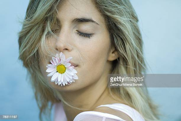 Woman holding flower in mouth, eyes closed, close-up