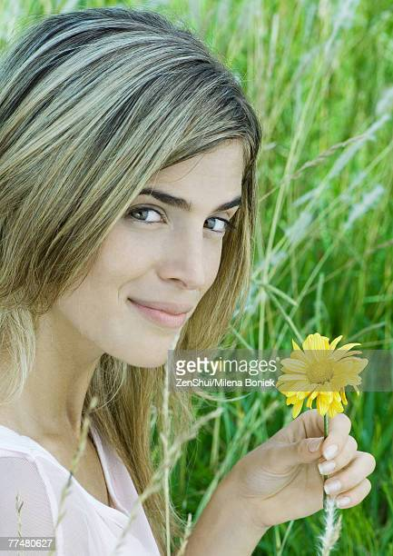 Woman holding flower, looking at camera