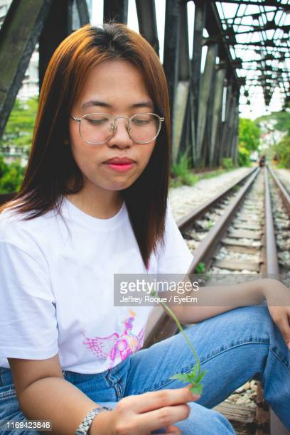 woman holding flower while sitting on railroad track - jeffrey roque stock photos and pictures