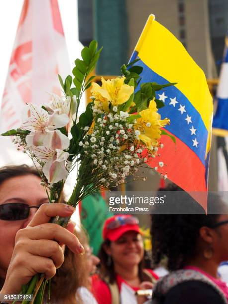 Woman holding flowers and a Venezuelan flag when thousands of Latin American left wing activists conducted an antiimperialist march against the...