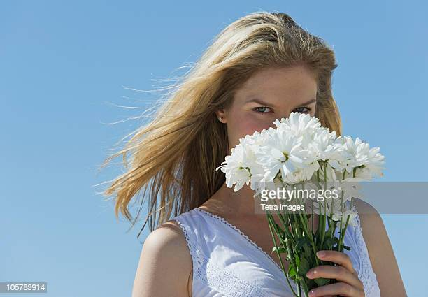 Woman holding flowers in front of her face