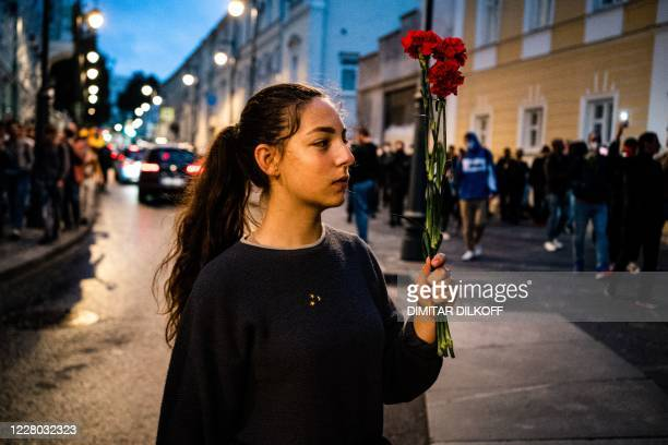 Woman holding flowers protests against the results of Belarusian presidential election outside the Belarusian embassy in Moscow on August 13, 2020.