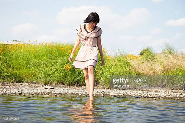 Woman holding flowers stepping into river