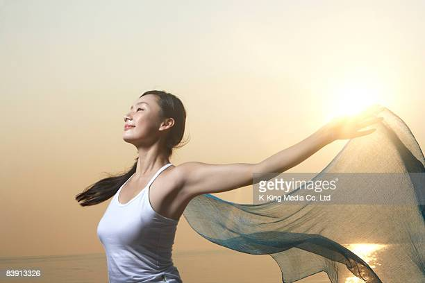 Woman holding flowing fabric.